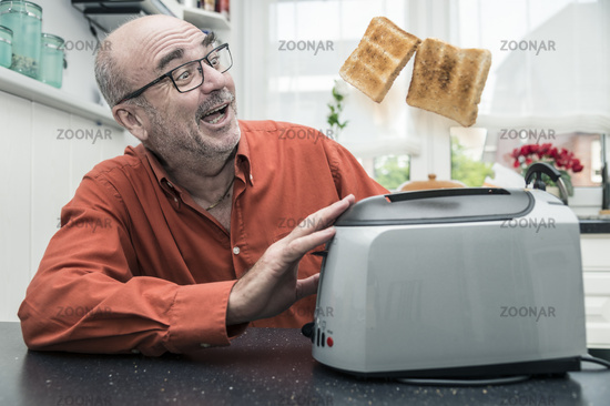man watches as jump 2 slices of toast from the toa