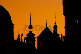 The silhouettes of towers and statues on Charles Bridge in Prague