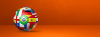 Football soccer ball with national flags on a orange studio banner