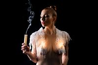 Naked female model with candles on breast
