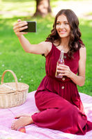 happy woman with smartphone taking selfie at park