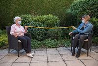 Senior woman and daughter with face masks measuring safety distance