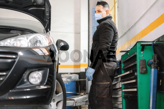 Professional mechanic with protective face mask, repairing a car in service garage.