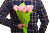 Man holding a bouquet of pink tulips behind his back, isolated on white background. Mothers day, Valentines day, love and surprise concept.