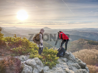 Photographer with tripod and camera on cliff and thinking