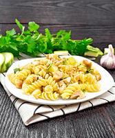 Fusilli with chicken and zucchini in plate on linen napkin