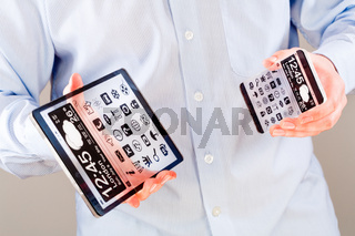 Smartphone and tablet with transparent screen in human hands.