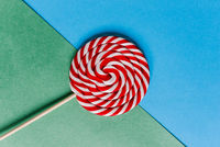 Lollipop with red and white spiral. Big round candy on a green and blue background. Caramel confectionery treat for adults and children. Retro style.