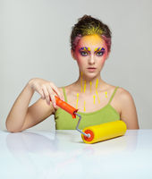Portrait of young woman posing at the table with paint roller in hand.