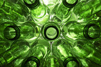 glass beer bottles lie in rows, necks on camera