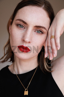 Attractive young woman with red lips wearing golden jewellery. Vertical close-up of beautiful woman.