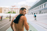 Young muscular guy with a naked torso looking back over his shoulder.