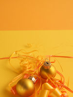 Golden vintage Christmas baubles on a yellow background