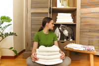 Cropped view of the woman wearing green t-shirt near cupboard holding towels in laundry room