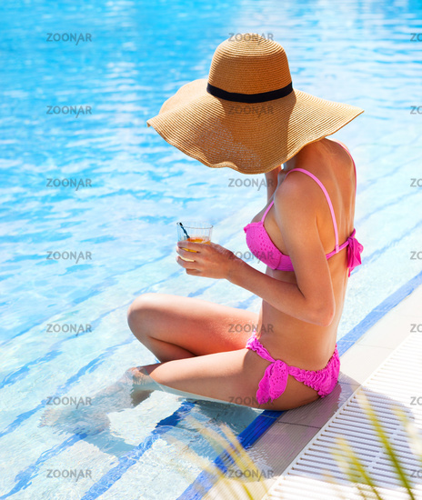 Woman in a hat enjoying cocktail in a swimming pool