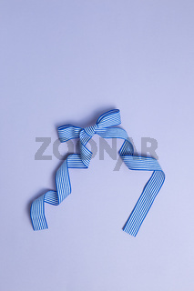 Striped pattern blue bow ribbon isolated on purple background