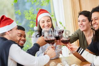 Freunde stoßen zur Weihnachtsfeier zwischen Nikolaus und Weihnachten an