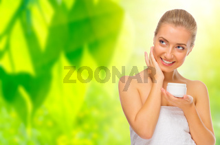 Young woman with body cream on floral background