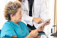 Doctor using tablet with old patient