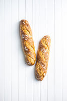 Two crispy fresh baguettes on white table.