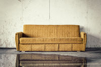 Discarded old brown sofa against dirty wall