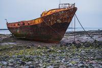 A rusty shipwreck in the mud, seen near Barrow-In-Furness, Cumbria, England