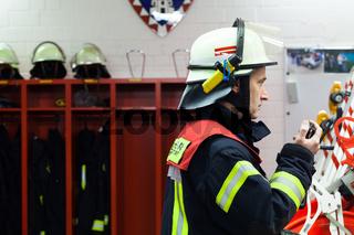 Feuerwehrmann in der Wache mit Funkgerät
