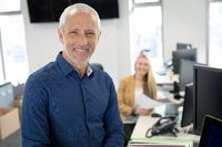 Portrait of senior businessman smiling at modern office