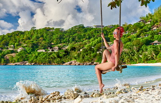 Woman swinging at tropical beach, Seychelles.