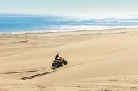 Quad driving people - One biker in sand desert dunes at ocean coast beach, Africa, Namibia, Namib, Walvis Bay, Swakopmund.