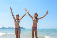 Two girls joyfully raised their hands up on the seashore