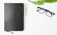 black notebook, pen and glasses on white table