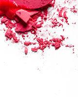 Crushed eyeshadows, lipstick and powder isolated on white background