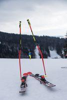 Ski poles and skis in the snow - skiers take a break