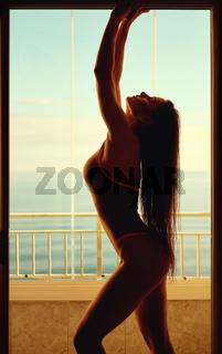 Fitness bikini model posing in summer terrace