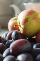 Plums and apples - autumnal fruits on the kitchen