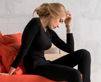 Slim blonde on a wooden sofa in a wistful pose