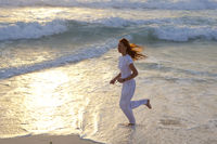 slender woman in a white tracksuit does a morning run along the edge of the waves on a sandy beach against the background of sunrise