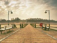 Old wood beach bridge in Goehren with nobody. Autumnal misty weather