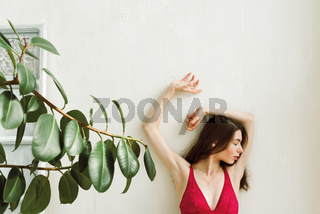 Young female in red bralette with her hands on the white wall, selective focus