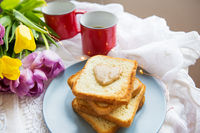 Homemade breakfast in bed. Toast with peanut butter, a cup of coffee and tulips. Good morning.
