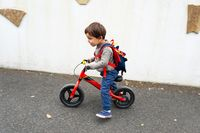Little boy rides his balance bike