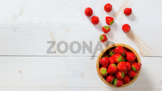 Red strawberries laying on white table from above with copy space.