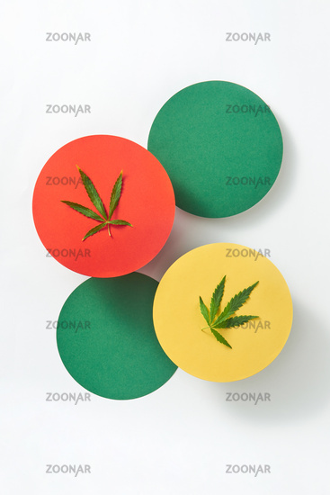 Multicolored round cards with marijuana leaves on a light grey background.