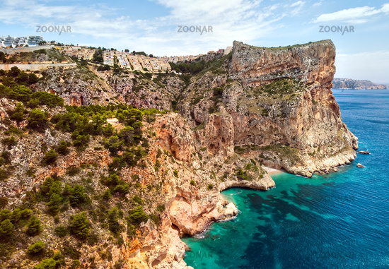 Aerial photo drone point of view picturesque Cala del Moraig in Benitachell coastal town. Bright turquoise waters bay of Mediterranean Sea white sandy beach, huge cliffs coastline. Costa Blanca. Spain