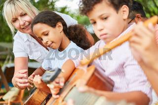 Kinder und Lehrerin im Gitarrenkurs im Ferienlager