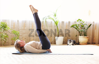 Mature woman stretching body on floor