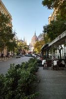 Town street with sidewalk cafe with view to Hungarian paliament building.