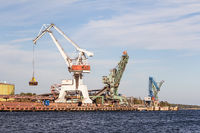 Working crane unload cargo in a seaport in Sweden