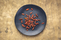dried goji berries on a black plate